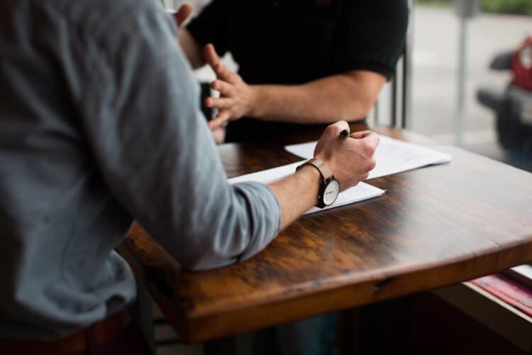 Darstellung eines Verkaufsgesprächs. Zu sehen sind zwei Personen während eines Gesprächs, welche an einem Tisch sitzen.